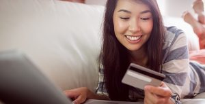 Woman on her computer looking at her credit card.